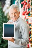 Man Displaying Digital Tablet In Christmas Store Stock Images