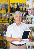 Man Displaying Digital Tablet In Hardware Store Royalty Free Stock Image