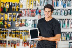Man Displaying Digital Tablet In Hardware Store. Portrait of smiling young man displaying digital tablet in hardware store Stock Photo