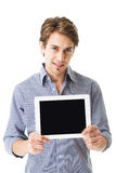 Man displaying his tablet-pc screen. Attractive young man displaying his blank black tablet-pc screen towards the camera while holding it against his chest stock photo