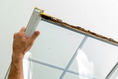 Man displaying a window damaged by wet rot Stock Photo