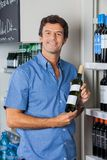 Man Displaying Wine Bottle In Supermarket Royalty Free Stock Image