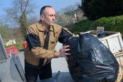 Man disposing black rubbish bag at tip. Man disposing of black rubbish bag at the tip Stock Photography