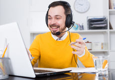 Man  distance learning. Young man runs distance learning and pleased solving problems in office Royalty Free Stock Photos