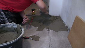 Man distribute mass tile glue on floor. Laser level measure stock video
