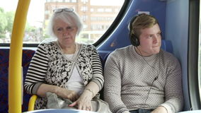 Man Disturbing Passengers On Bus Journey With Loud Music stock footage