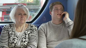 Man Disturbing Passengers On Bus Journey With Phone Call Royalty Free Stock Images