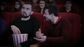 Man disturbs another person by talking in cinema stock video footage