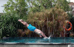 Man dive. In blue swimming pool stock photo