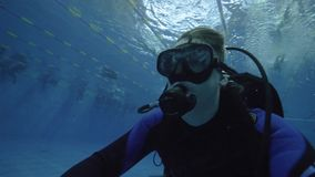 Man diver in scuba mask and diving equipment training in deep pool. Underwater diving in swimming pool. Scuba diver face underwater closeup stock video footage