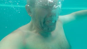 A man dives under the water in the pool and lets bubbles stock footage