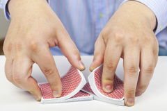 Man divided playing cards on table Stock Photos
