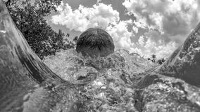 Man diving at the beach. Splash in the water.  Stock Images