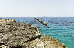 Man diving into the blue sea. Stock Photos
