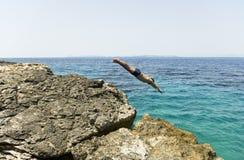 Man diving into the blue sea. Stock Photos