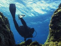 Man diving through the blue sea near of the seabed royalty free stock images