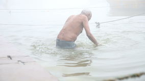 Man diving into Ganges river, surrounded with fog above water. stock video