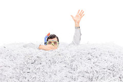 Man diving in a pile of shredded paper Stock Image