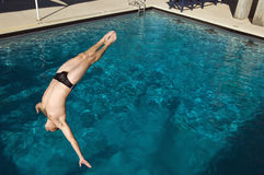 Man Diving Into The Pool. Active male swimmer diving into the pool Royalty Free Stock Photos