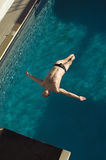 Man Diving Into The Pool. High angle view of a men diving in midair into the pool Royalty Free Stock Image