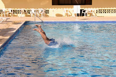 Man diving into pool. Headfirst with legs sticking out of the water royalty free stock image
