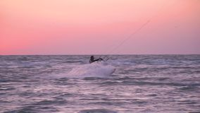A man kiter at dawn bounces over the waves. A man in a diving suit is engaged in kitesurfing, rushes through the waves at dawn and takes off into the air stock video