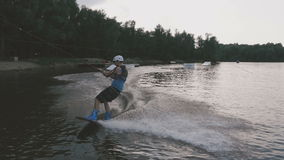 A man in a diving suit rides on the lake on a wakeboard. Young boy riding a wake board stock video footage