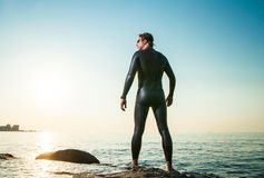 Man in diving suit standing in waves Stock Photo