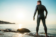 Man in diving suit standing in waves Stock Images