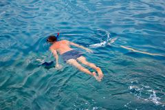 A man in a diving suit swims in the sea, top view. Activities on the water. Holday Stock Photo