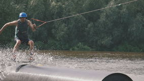 A man in a diving suit on the tube slides on wakeboard. Young boy riding a wake board stock footage