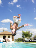 Man Diving Into Swimming Pool. Man upside down, diving into a swimming pool. Vertical Stock Photography