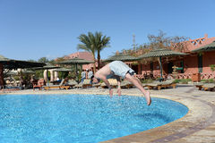 Man diving in a swimming pool. Side view of a man diving into a swimming pool Stock Photography