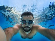 Diving to the pool. The man Diving to the pool and taking a selfie with swimming glasses Royalty Free Stock Photography