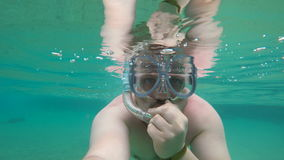 Man diving under water in sea in mask. In tropical country stock footage