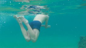 Man diving under water in sea in mask. In tropical country stock video footage