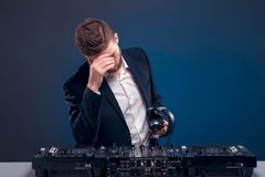 Closeup portrait of confident DJ with stylish hair style and headphones on neck mixing music on mixer while standing. Man DJ in dark suit play music on a Dj`s Stock Photos