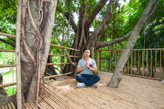 The man do meditation on the tree house Royalty Free Stock Images