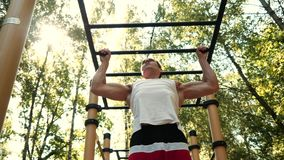 Man do pull ups in park. stock video footage