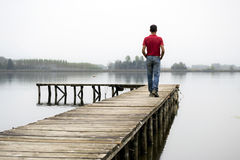 Man on dock. Man walking on a wooden dock on lake royalty free stock photo
