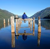 Man on a dock. A man sitting on an old broken wooden dock Stock Image