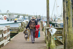 Man on dock with fishing gear. Westport, WA, USA August 21, 2016: Fisherman with fishing gear and crab pot walks along dock among boats at Westport, Washington Royalty Free Stock Photo