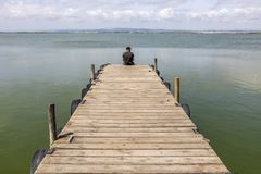 Man On A Dock By The Lake At morning Sky royalty free stock images
