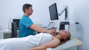 Man doctor diagnostic thyroid gland of ung woman using ultrasound scanner.