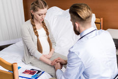 Man doctor reassuring upset pregnant woman sitting on hospital bed Stock Image