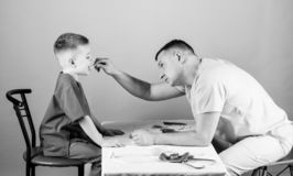 Man doctor sit table medical tools examining little boy patient. Health care. Pediatrician concept. Child care. Careful stock photo