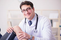 The man doctor taking care of sports injury Stock Photos