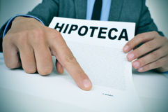 Man with a document with the word hipoteca, mortgage loan contra Royalty Free Stock Images