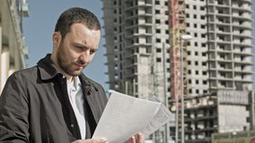 Man with documentation near construction of a new. Building. Professional shot on BMCC with high dynamic range. You can use it e.g in your commercial video stock footage