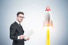 Man with documents and rocket. Businessman in glasses is standing with documents near a gray wall with a large launching rocket on it Stock Images